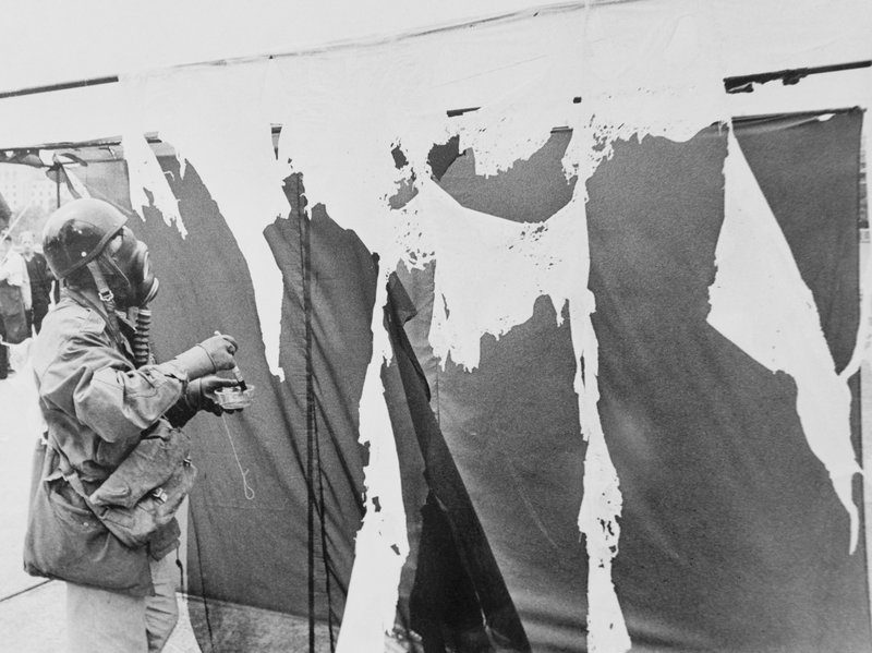 Metzger wears a gas mask while painting three nylon curtains with hydrochloric acid, causing them to disintegrate,in 1961
